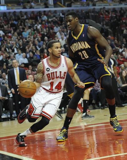 Mar 24, 2014; Chicago, IL, USA;  Chicago Bulls guard D.J. Augustin (14) is defended by Indiana Pacers center Ian Mahinmi (28) during the second quarter at the United Center. Mandatory Credit: David Banks-USA TODAY Sports