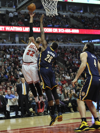 Mar 24, 2014; Chicago, IL, USA;  Chicago Bulls forward Taj Gibson (22) is defended by Indiana Pacers center Ian Mahinmi (28) during the second quarter  at the United Center. Mandatory Credit: David Banks-USA TODAY Sports