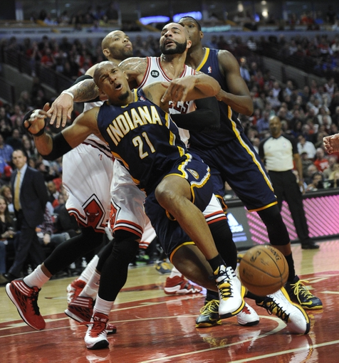 Mar 24, 2014; Chicago, IL, USA; Indiana Pacers forward David West (21) is fouled by Chicago Bulls forward Carlos Boozer (5) during the second half at the United Center. the Chicago Bulls defeated the Indiana Pacers 89-77. Mandatory Credit: David Banks-USA TODAY Sports