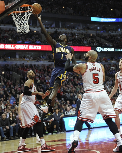 Mar 24, 2014; Chicago, IL, USA; Indiana Pacers guard Lance Stephenson (1) is defended by Chicago Bulls forward Carlos Boozer (5) during the second half at the United Center. the Chicago Bulls defeated the Indiana Pacers 89-77. Mandatory Credit: David Banks-USA TODAY Sports