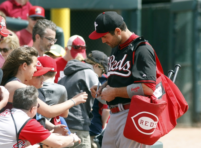 Mar 26, 2014; Phoenix, AZ, USA; Cincinnati Reds first baseman Joey Votto (19) signs autographs for fans before a game against the Chicago White Sox at Camelback Ranch. Mandatory Credit: Rick Scuteri-USA TODAY Sports