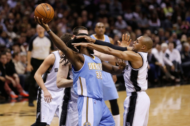 Mar 26, 2014; San Antonio, TX, USA; Denver Nuggets forward Kenneth Faried (35) passes the ball as San Antonio Spurs guard Patrick Mills (right) defends during the first half at AT&T Center. Mandatory Credit: Soobum Im-USA TODAY Sports