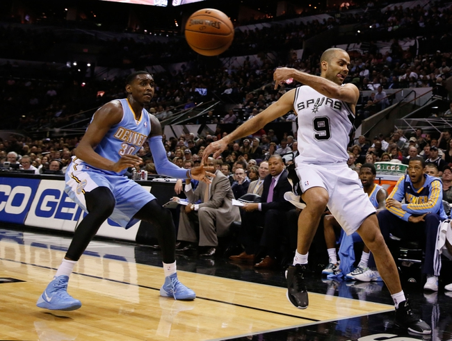 Mar 26, 2014; San Antonio, TX, USA; San Antonio Spurs guard Tony Parker (9) tries to save a ball from going out of bounds during the first half against the Denver Nuggets at AT&T Center. Mandatory Credit: Soobum Im-USA TODAY Sports