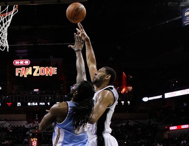 Mar 26, 2014; San Antonio, TX, USA; San Antonio Spurs forward Tim Duncan (21) shoots the ball over Denver Nuggets forward Kenneth Faried (35) during the first half at AT&T Center. Mandatory Credit: Soobum Im-USA TODAY Sports