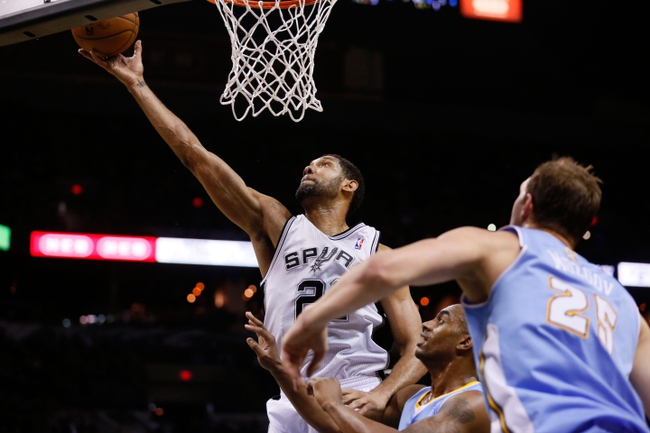 Mar 26, 2014; San Antonio, TX, USA; San Antonio Spurs forward Tim Duncan (21) shoots the ball past Denver Nuggets forward Darrell Arthur (center) and Timofey Mozgov (right) during the second half at AT&T Center. The Spurs won 108-103. Mandatory Credit: Soobum Im-USA TODAY Sports