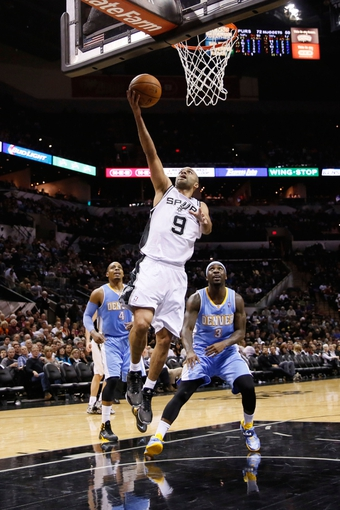 Mar 26, 2014; San Antonio, TX, USA; San Antonio Spurs guard Tony Parker (9) drives to the basket past Denver Nuggets guard Ty Lawson (3) during the second half at AT&T Center. The Spurs won 108-103. Mandatory Credit: Soobum Im-USA TODAY Sports