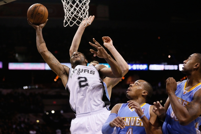 Mar 26, 2014; San Antonio, TX, USA; San Antonio Spurs forward Kawhi Leonard (2) shoots the ball past Denver Nuggets guard Randy Foye (center) and forward Darrell Arthur (right) during the second half at AT&T Center. The Spurs won 108-103. Mandatory Credit: Soobum Im-USA TODAY Sports