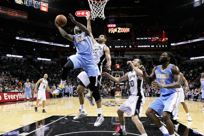 Mar 26, 2014; San Antonio, TX, USA; Denver Nuggets guard Ty Lawson (3) shoots the ball as San Antonio Spurs forward Tim Duncan (21) defends during the second half at AT&T Center. The Spurs won 108-103. Mandatory Credit: Soobum Im-USA TODAY Sports
