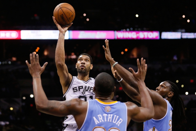 Mar 26, 2014; San Antonio, TX, USA; San Antonio Spurs forward Tim Duncan (21) shoots the ball over Denver Nuggets forward Darrell Arthur (0) and Kenneth Faried (right) during the second half at AT&T Center. The Spurs won 108-103. Mandatory Credit: Soobum Im-USA TODAY Sports