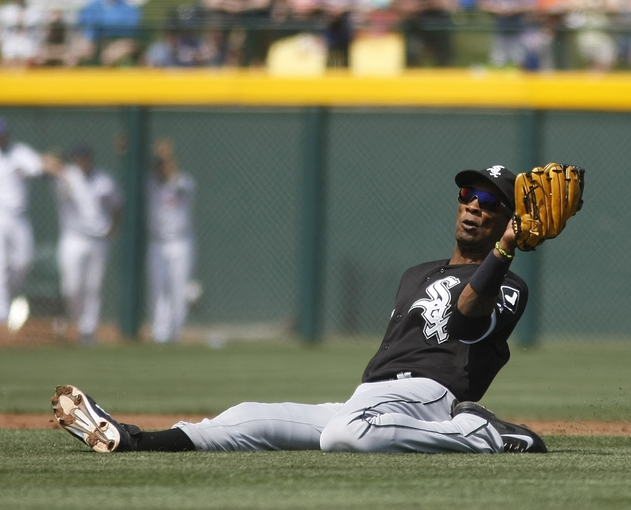 Mar 27, 2014; Mesa, AZ, USA; Chicago White Sox shortstop Alexei Ramirez (10) makes the sliding catch against the Chicago Cubs in the fourth inning at HoHoKam Park. Mandatory Credit: Rick Scuteri-USA TODAY Sports