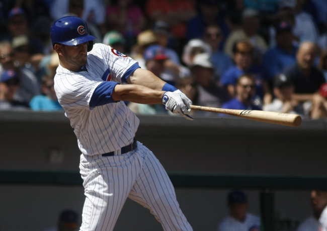 Mar 27, 2014; Mesa, AZ, USA; Chicago Cubs left fielder Justin Ruggiano (20) hits an RBI double in the fourth inning against the Chicago White Sox at HoHoKam Park. Mandatory Credit: Rick Scuteri-USA TODAY Sports