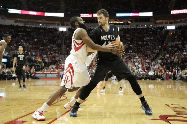 Mar 20, 2014; Houston, TX, USA; Minnesota Timberwolves forward Kevin Love (42) is defended by Houston Rockets guard James Harden (13) during the third quarter at Toyota Center. Mandatory Credit: Andrew Richardson-USA TODAY Sports