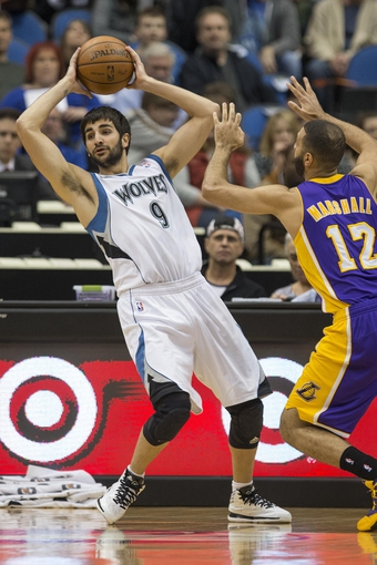 Mar 28, 2014; Minneapolis, MN, USA; Minnesota Timberwolves guard Ricky Rubio (9) looks to pass the ball in front of Los Angeles Lakers guard Kendall Marshall (12) in the first half at Target Center. Mandatory Credit: Jesse Johnson-USA TODAY Sports