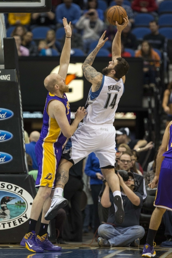 Mar 28, 2014; Minneapolis, MN, USA; Minnesota Timberwolves center Nikola Pekovic (14) shoots the ball as Los Angeles Lakers center Chris Kaman (9) defends in the first half at Target Center. Mandatory Credit: Jesse Johnson-USA TODAY Sports