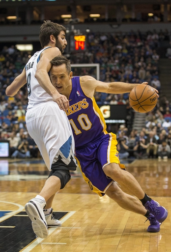 Mar 28, 2014; Minneapolis, MN, USA; Los Angeles Lakers guard Steve Nash (10) dribbles the ball around Minnesota Timberwolves guard Ricky Rubio (9) in the first half at Target Center. Mandatory Credit: Jesse Johnson-USA TODAY Sports