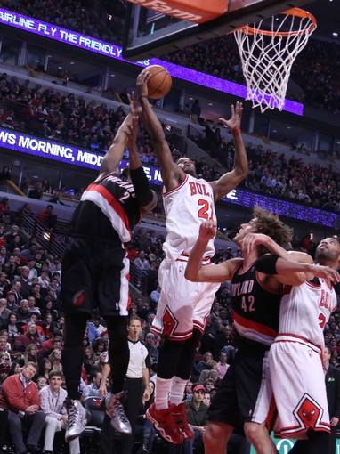 Mar 28, 2014; Chicago, IL, USA; Chicago Bulls guard Jimmy Butler (21) rebounds over Portland Trail Blazers guard Wesley Matthews (2) during the second quarter at the United Center. Mandatory Credit: Dennis Wierzbicki-USA TODAY Sports
