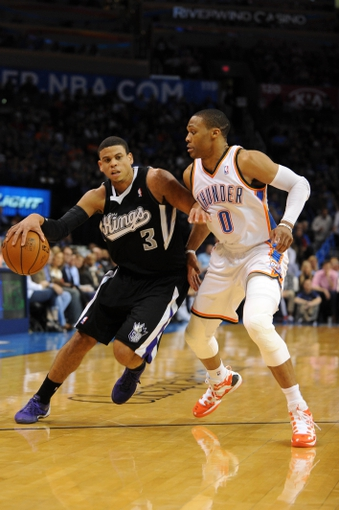Mar 28, 2014; Oklahoma City, OK, USA; Sacramento Kings guard Ray McCallum (3) handles the ball against Oklahoma City Thunder guard Russell Westbrook (0) during the second quarter at Chesapeake Energy Arena. Mandatory Credit: Mark D. Smith-USA TODAY Sports