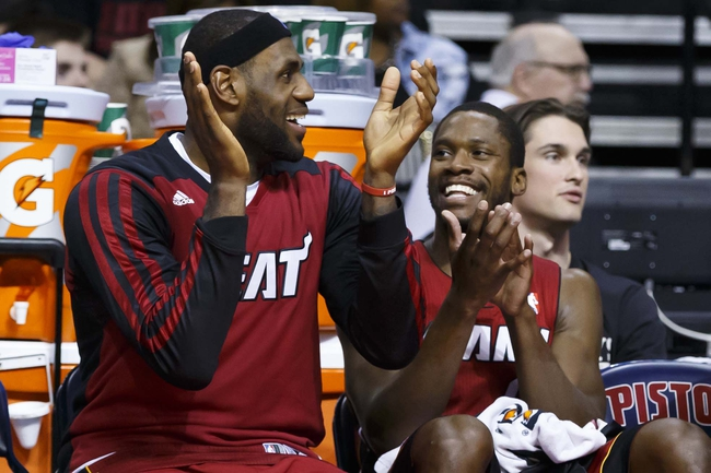 Mar 28, 2014; Auburn Hills, MI, USA; Miami Heat forward LeBron James (6) and guard Toney Douglas (0) clap while on the bench during the fourth quarter against the Detroit Pistons at The Palace of Auburn Hills. Mandatory Credit: Rick Osentoski-USA TODAY Sports