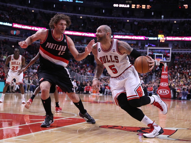 Mar 28, 2014; Chicago, IL, USA; Chicago Bulls forward Carlos Boozer (5) drives against Portland Trail Blazers center Robin Lopez (42) during the second half at the United Center. Portland won 91-74. Mandatory Credit: Dennis Wierzbicki-USA TODAY Sports