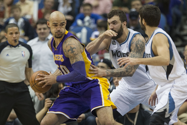 Mar 28, 2014; Minneapolis, MN, USA; Los Angeles Lakers center Robert Sacre (50) looks to drive to the basket past Minnesota Timberwolves center Nikola Pekovic (14) in the second half at Target Center. The Timberwolves won 143-107. Mandatory Credit: Jesse Johnson-USA TODAY Sports