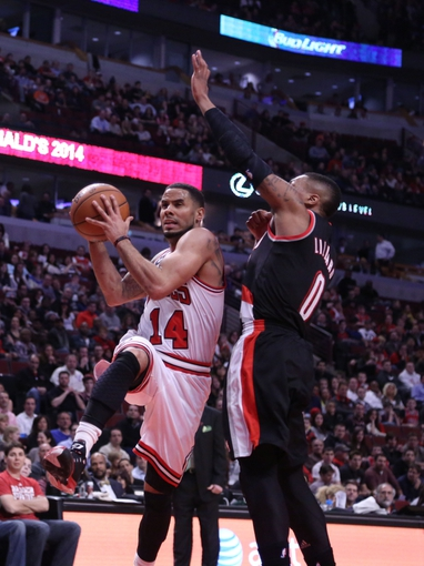 Mar 28, 2014; Chicago, IL, USA; Chicago Bulls guard D.J. Augustin (14) drives against Portland Trail Blazers guard Damian Lillard (0) during the second half at the United Center. Portland won 91-74. Mandatory Credit: Dennis Wierzbicki-USA TODAY Sports
