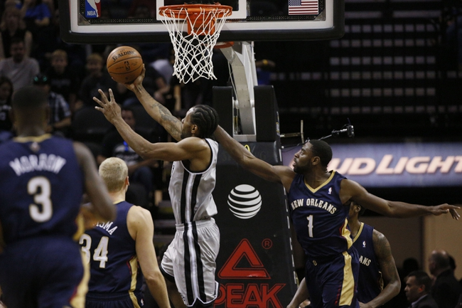 Mar 29, 2014; San Antonio, TX, USA; San Antonio Spurs forward Kawhi Leonard (2) shoots the ball past New Orleans Pelicans forward Tyreke Evans (1) during the first half at AT&T Center. Mandatory Credit: Soobum Im-USA TODAY Sports