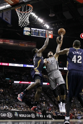 Mar 29, 2014; San Antonio, TX, USA; San Antonio Spurs forward Marco Belinelli (3) shoots while being defended by New Orleans Pelicans forward Tyreke Evans (left) during the second half at AT&T Center. The Spurs won 96-80. Mandatory Credit: Soobum Im-USA TODAY Sports