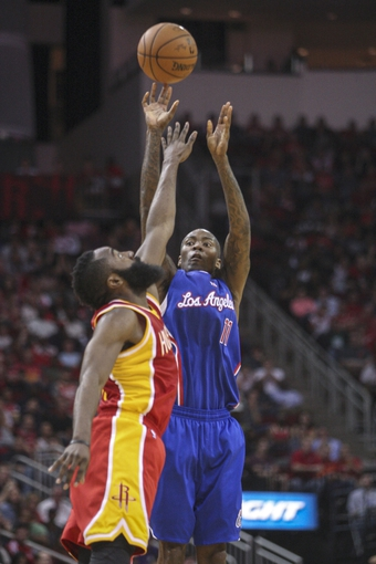 Mar 29, 2014; Houston, TX, USA; Los Angeles Clippers guard Jamal Crawford (11) shoots during the fourth quarter as Houston Rockets guard James Harden (13) defends at Toyota Center. The Clippers defeated the Rockets 118-107. Mandatory Credit: Troy Taormina-USA TODAY Sports