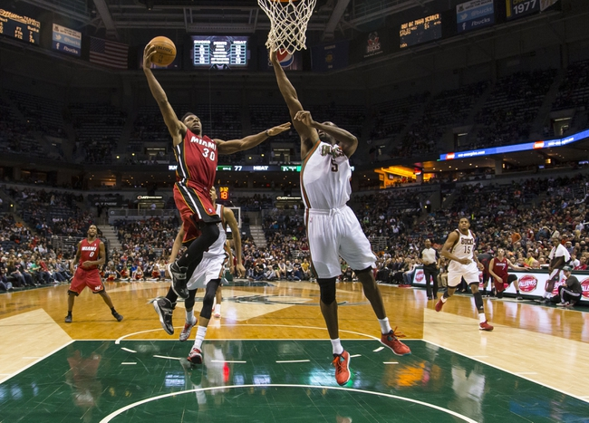 Mar 29, 2014; Milwaukee, WI, USA; Miami Heat guard Norris Cole (30) drives for the basket as Milwaukee Bucks forward Ekpe Udoh (5) defends during the fourth quarter at BMO Harris Bradley Center.  Miami won 88-67.  Mandatory Credit: Jeff Hanisch-USA TODAY Sports