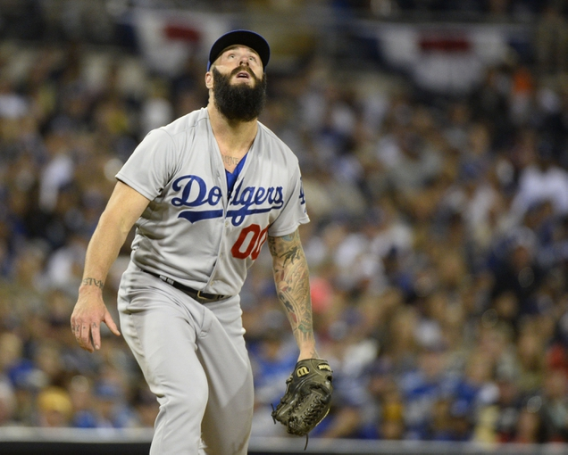 Mar 30, 2014; San Diego, CA, USA; Los Angeles Dodgers relief pitcher Brian Wilson (0) watches a home run hit by San Diego Padres pinch hitter Seth Smith (not pictured) in the eighth inning on the opening day baseball game at Petco Park. Mandatory Credit: Christopher Hanewinckel-USA TODAY Sports
