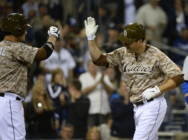 Mar 30, 2014; San Diego, CA, USA; San Diego Padres pinch hitter Seth Smith (12) celebrates with catcher Yasmani Grandal (8) following a solo home run in the eighth inning  on the opening day baseball game against the Los Angeles Dodgers at Petco Park. Mandatory Credit: Christopher Hanewinckel-USA TODAY Sports