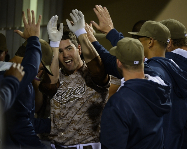 Mar 30, 2014; San Diego, CA, USA; San Diego Padres pinch hitter Seth Smith (12) celebrates with teammates in the dugout following a solo home run in the eighth inning  on the opening day baseball game against the Los Angeles Dodgers at Petco Park. Mandatory Credit: Christopher Hanewinckel-USA TODAY Sports
