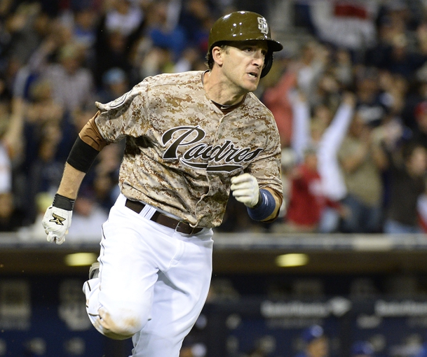 Mar 30, 2014; San Diego, CA, USA; San Diego Padres right fielder Chris Denorfia (13) singles home two runs in the eighth inning  on the opening day baseball game against the Los Angeles Dodgers at Petco Park. Mandatory Credit: Christopher Hanewinckel-USA TODAY Sports
