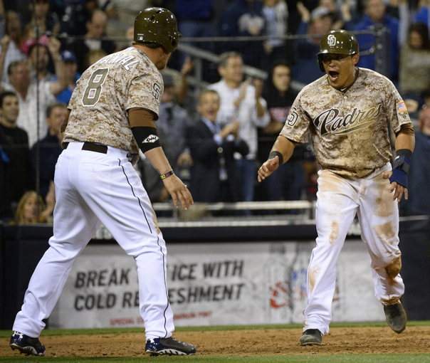 Mar 30, 2014; San Diego, CA, USA; San Diego Padres shortstop Everth Cabrera (2) celebrates with catcher Yasmani Grandal (8) after scoring in the eighth inning on the opening day baseball game against the Los Angeles Dodgers at Petco Park. Mandatory Credit: Christopher Hanewinckel-USA TODAY Sports