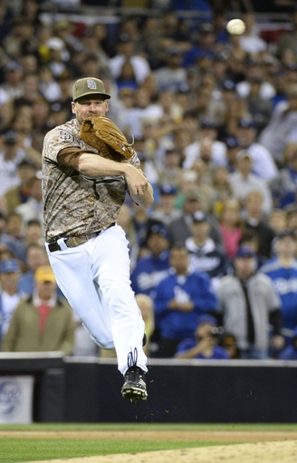 Mar 30, 2014; San Diego, CA, USA; San Diego Padres third baseman Chase Headley (7) throws the ball to first of the ninth inning  on the opening day baseball game against the Los Angeles Dodgers at Petco Park. The Padres won 3-1. Mandatory Credit: Christopher Hanewinckel-USA TODAY Sports