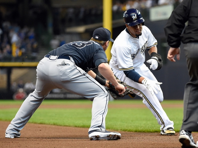 Mar 31, 2014; Milwaukee, WI, USA;   Milwaukee Brewers center fielder Carlos Gomez (27) tries to stretch out a single and is tagged out by Atlanta Braves third baseman Chris Johnson (23) after advancing to second base on an error in the first inning of an opening day baseball game at Miller Park. Mandatory Credit: Benny Sieu-USA TODAY Sports
