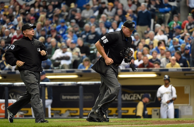 Mar 31, 2014; Milwaukee, WI, USA;   Home plate umpire Ted Barret (right) and first base umpire Greg Gibson stops play to look at instant replay after a close call at first base was challenged in the sixth inning during game between the Milwaukee Brewers and Atlanta Braves of an opening day baseball game at Miller Park. Mandatory Credit: Benny Sieu-USA TODAY Sports