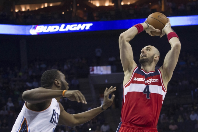 Mar 31, 2014; Charlotte, NC, USA; Washington Wizards center Marcin Gortat (4) shoots the ball over Charlotte Bobcats center Al Jefferson (25) during the first half at Time Warner Cable Arena. Mandatory Credit: Jeremy Brevard-USA TODAY Sports