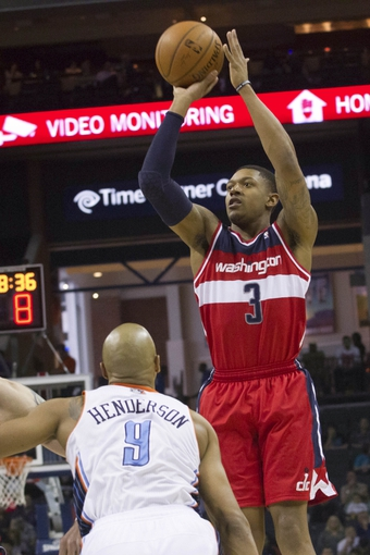 Mar 31, 2014; Charlotte, NC, USA;  Washington Wizards guard Bradley Beal (3) shoots a three point shot over Charlotte Bobcats guard Gerald Henderson (9) during the first half at Time Warner Cable Arena. Mandatory Credit: Jeremy Brevard-USA TODAY Sports