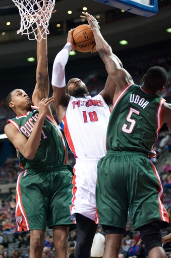 Mar 31, 2014; Auburn Hills, MI, USA; Detroit Pistons forward Greg Monroe (10) shoots the ball between Milwaukee Bucks center John Henson (31) and forward Ekpe Udoh (5) during the first quarter at The Palace of Auburn Hills. Mandatory Credit: Tim Fuller-USA TODAY Sports
