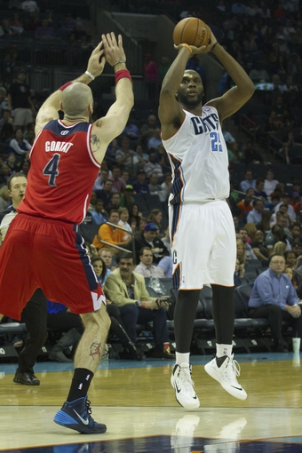 Mar 31, 2014; Charlotte, NC, USA; Charlotte Bobcats center Al Jefferson (25) shoots the ball over Washington Wizards center Marcin Gortat (4) during the second half at Time Warner Cable Arena. Bobcats defeated the Wizards 100-94. Mandatory Credit: Jeremy Brevard-USA TODAY Sports