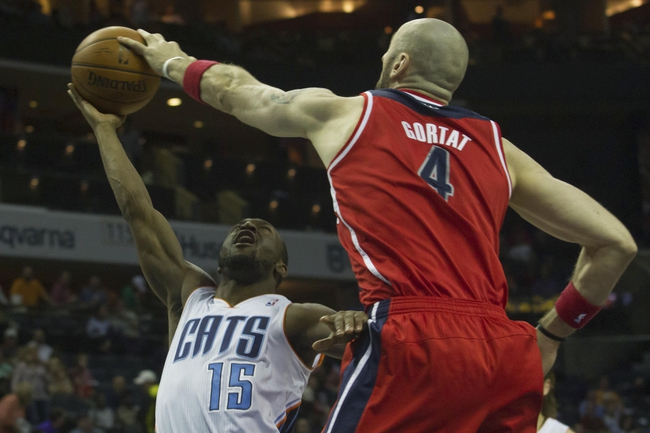 Mar 31, 2014; Charlotte, NC, USA; Washington Wizards center Marcin Gortat (4) blocks the shot of Charlotte Bobcats guard Kemba Walker (15) during the second half at Time Warner Cable Arena. Bobcats defeated the Wizards 100-94. Mandatory Credit: Jeremy Brevard-USA TODAY Sports