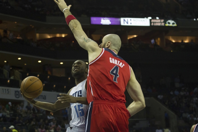 Mar 31, 2014; Charlotte, NC, USA; Charlotte Bobcats guard Kemba Walker (15) shoots the ball around Washington Wizards center Marcin Gortat (4) during the second half at Time Warner Cable Arena. Bobcats defeated the Wizards 100-94. Mandatory Credit: Jeremy Brevard-USA TODAY Sports