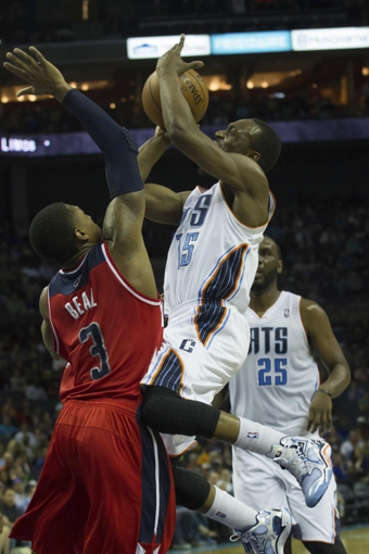 Mar 31, 2014; Charlotte, NC, USA; Charlotte Bobcats guard Kemba Walker (15) shoots the ball over Washington Wizards guard Bradley Beal (3) during the second half at Time Warner Cable Arena. Bobcats defeated the Wizards 100-94. Mandatory Credit: Jeremy Brevard-USA TODAY Sports