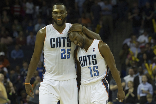 Mar 31, 2014; Charlotte, NC, USA; Charlotte Bobcats guard Kemba Walker (15) celebrates with center Al Jefferson (25) during the second half against the Washington Wizards at Time Warner Cable Arena. Bobcats defeated the Wizards 100-94. Mandatory Credit: Jeremy Brevard-USA TODAY Sports