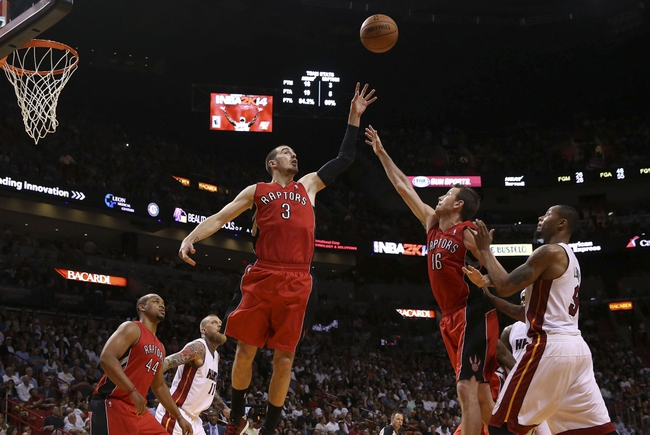 Mar 31, 2014; Miami, FL, USA; Toronto Raptors guard Nando de Colo (3) and forward Steve Novak (16) battle for a rebound as Miami Heat forward Rashard Lewis (9) looks on in the second half at American Airlines Arena. The Heat won 93-83. Mandatory Credit: Robert Mayer-USA TODAY Sports