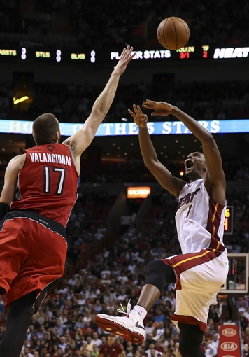 Mar 31, 2014; Miami, FL, USA;  Miami Heat center Chris Bosh (1) has a shot blocked by Toronto Raptors center Jonas Valanciunas (17) in the second half at American Airlines Arena. The Heat won 93-83. Mandatory Credit: Robert Mayer-USA TODAY Sports