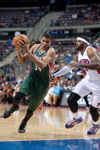 Mar 31, 2014; Auburn Hills, MI, USA; Milwaukee Bucks guard Giannis Antetokounmpo (34) dribbles the ball around Detroit Pistons forward Josh Smith (6) during the fourth quarter at The Palace of Auburn Hills. Pistons won 116-111. Mandatory Credit: Tim Fuller-USA TODAY Sports