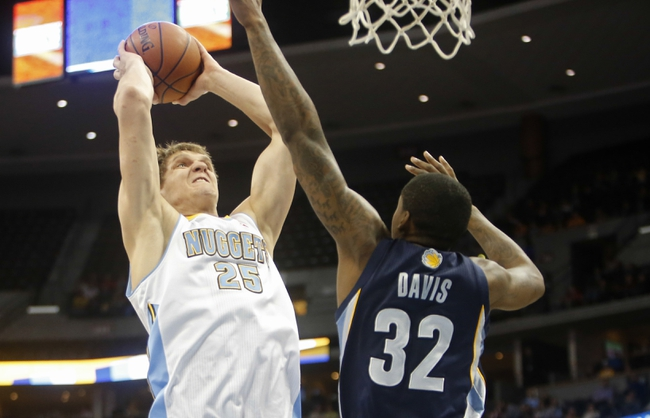 Mar 31, 2014; Denver, CO, USA; Denver Nuggets center Timofey Mozgov (25) dunks the ball over Memphis Grizzlies forward Ed David (32)  during the first half at Pepsi Center. Mandatory Credit: Chris Humphreys-USA TODAY Sports
