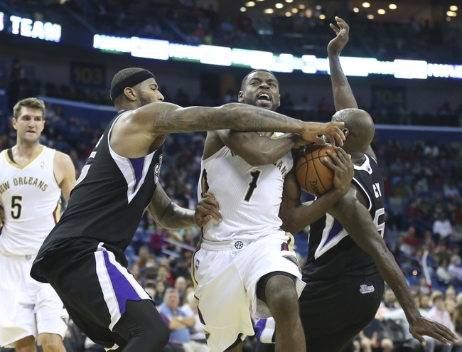Mar 31, 2014; New Orleans, LA, USA; New Orleans Pelicans forward Tyreke Evans (1) is defended by Sacramento Kings forward Quincy Acy (right) and center DeMarcus Cousins (left) in the second half at the Smoothie King Center. Sacramento defeated New Orleans 102-97. Mandatory Credit: Crystal LoGiudice-USA TODAY Sports